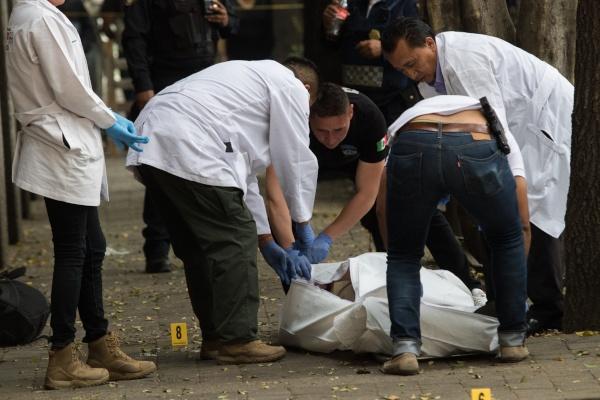 peritos levantando cuerpo en asalto a periodista.