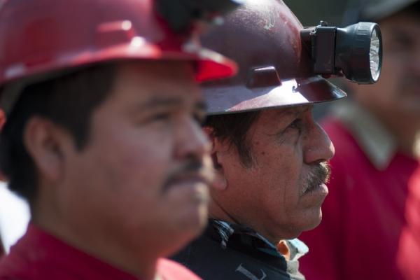 Dos mineros de perfil usando cascos