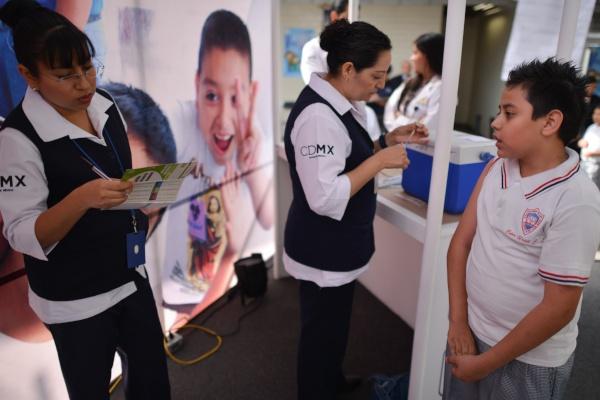 enfermeras vacunando niños en escuela.