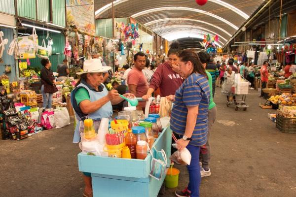 Mujer de la tercera edad vendiendo raspados en un mercado, un hombre comprando