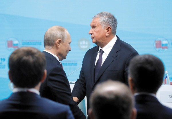 El mandatario ruso, Vladimir Putin, saluda al director ejecutivo de Rosneft, Igor Sechin. Foto: Reuters