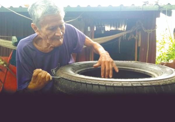 Mariano López corta la llanta de acuerdo con la cantidad de suelas que elaborará en su taller de huaraches, en Juchitán, Oaxaca. Foto: José Luis López