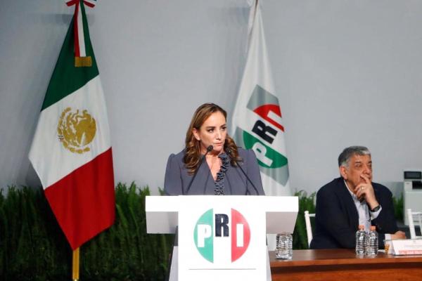 Claudia Ruiz Massieu en pódium con bandera del PRI