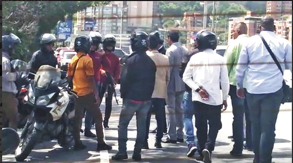 MEDIACIÓN. Un video muestra a Guaidó (traje gris) dialogando con hombres armados. Foto: Especial
