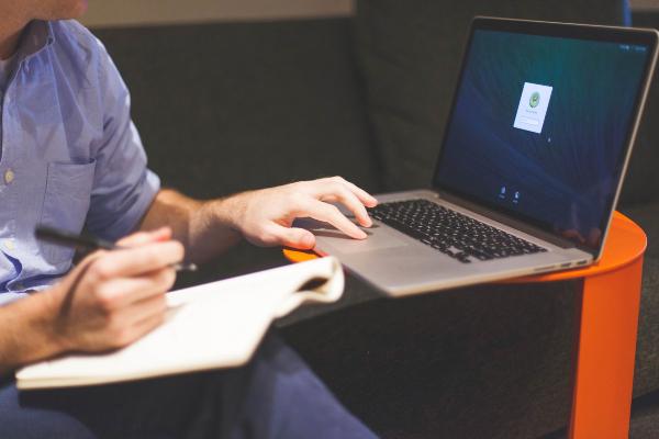 Persona escribiendo en un cuaderno con una mano y la otra en una computadora