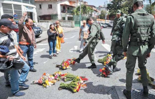Militares patean ofrendas florales llevadas en honor al capitán a instalaciones de la Armada Bolivariana.  Foto: EFE