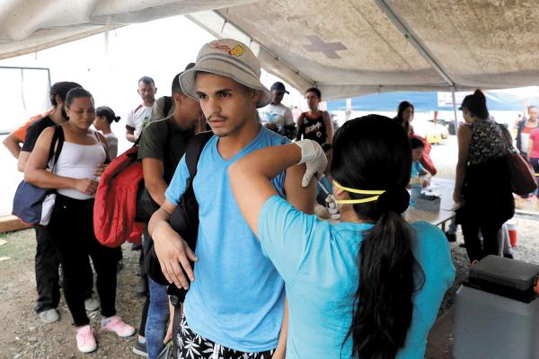 PERÚ. Migrantes venezolanos fueron vacunados por los servicios fronterizos de ese país. Foto: AP