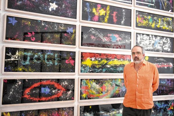 OBRA. El artista posa frente a las obras que realizaron los niños durante su taller. Foto: Leslie Pérez.