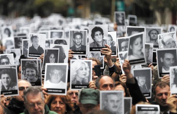 MEMORIA. Centenares de personas mostraron fotografías con los rostros de las víctimas. Foto: REUTERS.