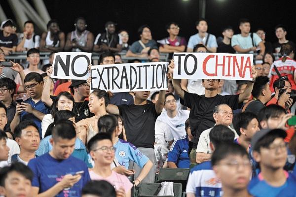 ESTADIO. Opositores se manifestaron ayer, en medio de un partido de futbol, en Hong Kong. Foto: FP.