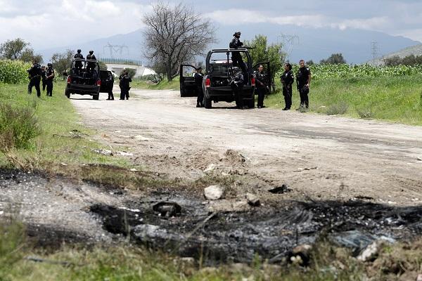 Policía federal resguarda la zona y dos camionetas de Seguridad Física de Pemex que fueron incendiadas por presuntos