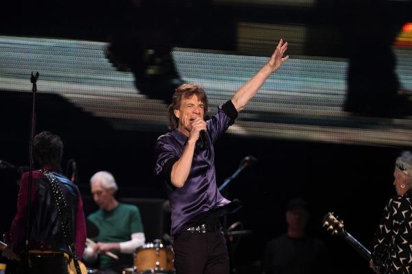 Mick Jagger en concierto cantando y levantando la mano