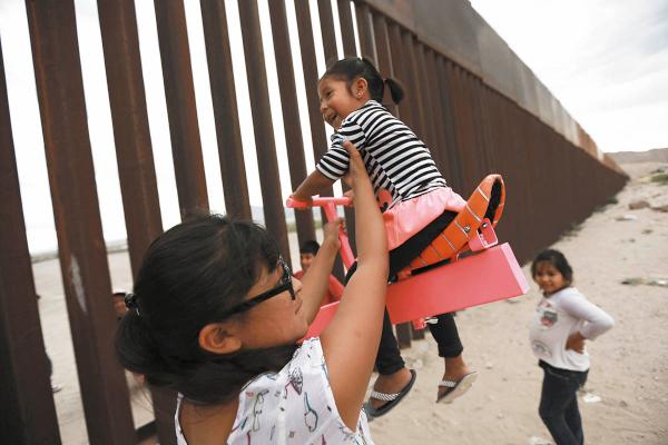 UNIÓN. Niños y adultos juegan en ambos lados de la frontera. Foto: AP.