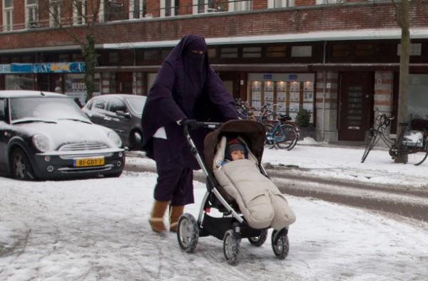 TRADICIÓN. Una mujer con el rostro cubierto camina con su bebé por las calles de Ámsterdam. Foto: AP