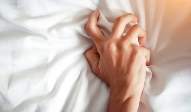 Una mano femenina sobre las sábanas blancas. FOTO: Shutterstock.