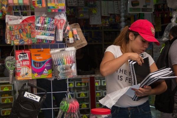 Mujer con útiles escolares a un lado mientras ve libretas
