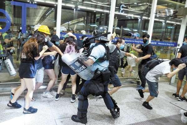 VIOLENCIA. Agentes confrontaron a manifestantes que bloquearon la terminal del aeropuerto. Foto: REUTERS