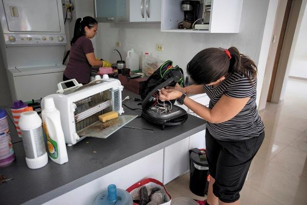 REALIDAD. Dos profesionistas dan mantenimiento en una casa deshabitada, en Caracas. Foto: EFE.