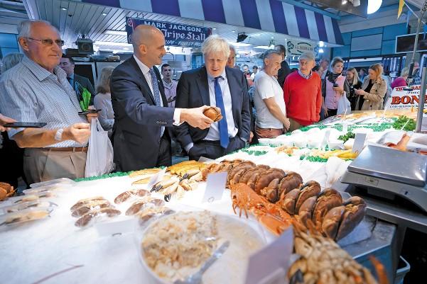 INGLATERRA. Boris Johnson, en un mercado de pescado, en riesgo por el Brexit. Foto: AP