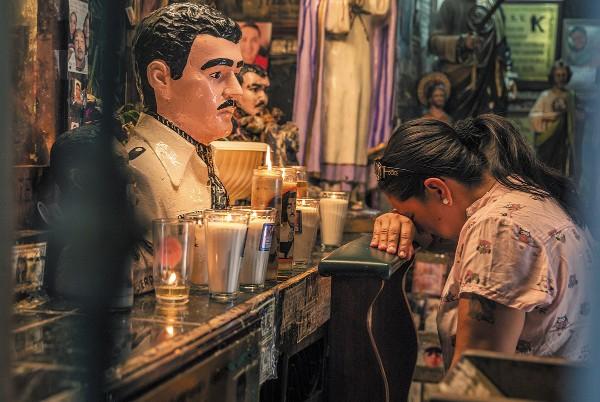 PLEGARIAS. Una mujer acude al altar de Malverde para hacer un pedido. Foto: Cuartoscuro