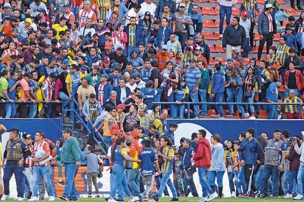 INCIDENTE. Los aficionados que estaban abajo de la barra queretana fueron bajados a la cancha. Foto: Mexsport