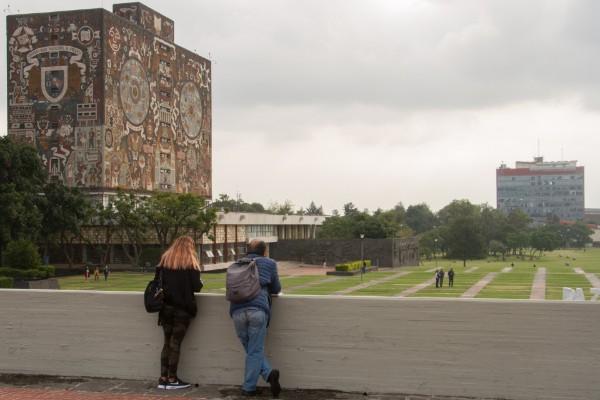Una pareja observa desde la explanada de la Rectoría de la Universidad Autónoma de México a los alumnos y personal de la UNAM mientras caminan por las islas ubicadas en Ciudad Universitaria. FOTO: ROGELIO MORALES /CUARTOSCURO.COM
