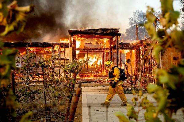 DESASTRE. Bomberos laboran en una casa envuelta en llamas. Foto: AP