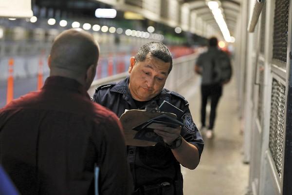 TRÁMITE. Un oficial de Aduanas verifica los documentos de un migrante que solicita asilo. Foto: AP
