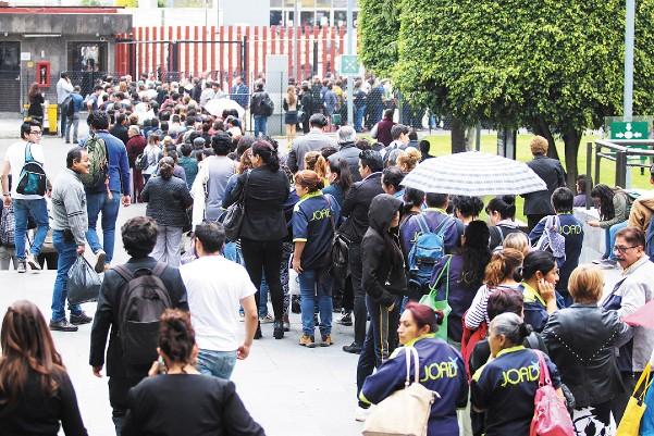 BLOQUEO. Trabajadores de San Lázaro hicieron fila ayer para salir del recinto, debido al bloqueo que hizo un grupo de químicos. Foto: Cuartoscuro