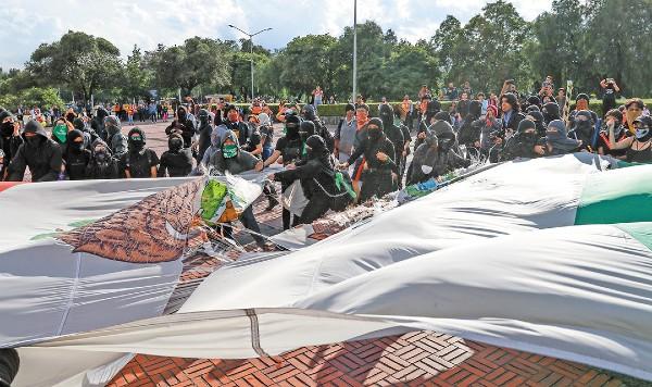 ULTRAJE. El grupo de encapuchados bajó, rompió y luego quemó la bandera de México. Foto: Cuartoscuro