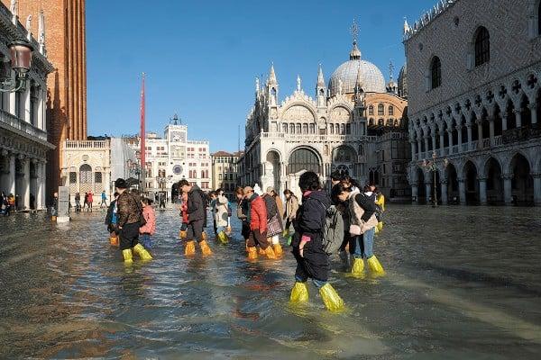 DESASTRE. Los turistas caminaron por la inundada Plaza de San Marcos. Foto: REUTERS