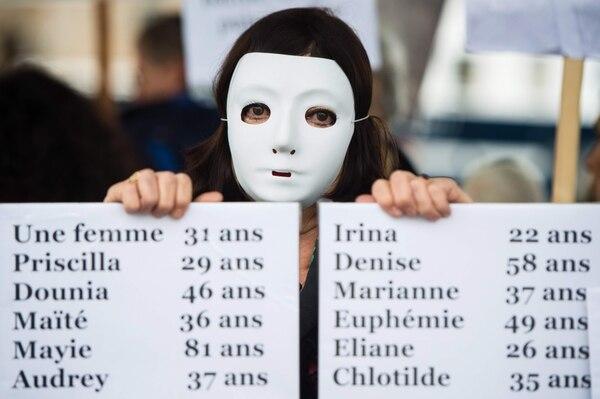 DENUNCIA. Una mujer muestra lista de muertas. Foto: AFP