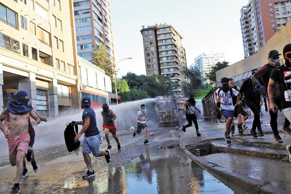 CHOQUES. Con chorros de agua evitaron el paso de los quejosos. Foto: Reuters
