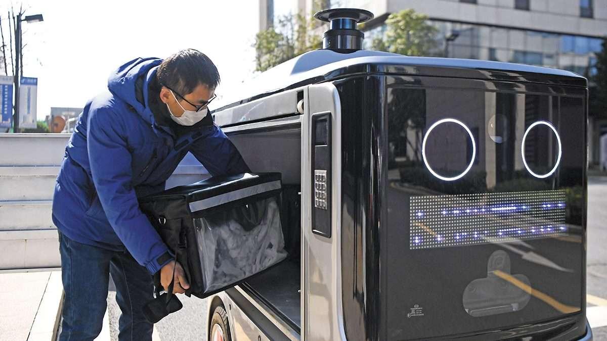 CAMBIOS. Un trabajador colocó alimentos en el interior de un robot repartirdor en Changsha, China. Foto: XINHUA