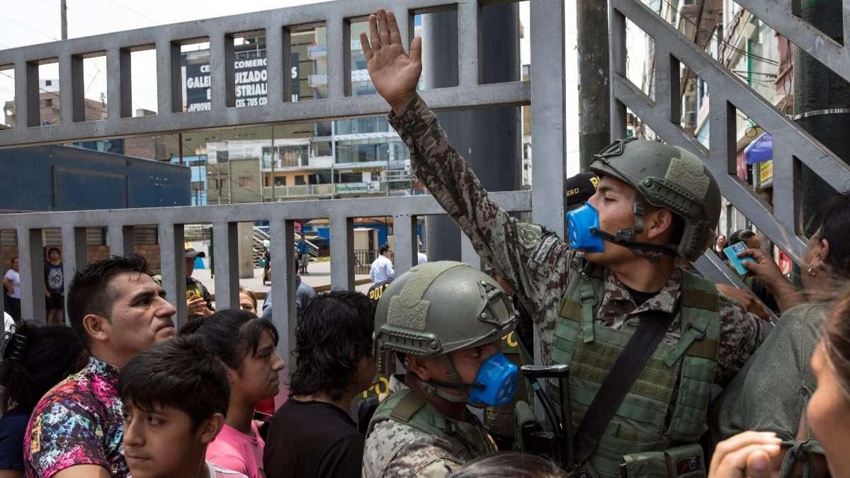 TRABAJOS. Soldados organizan a las personas en un mercado de ropa en Perú. Foto: AP