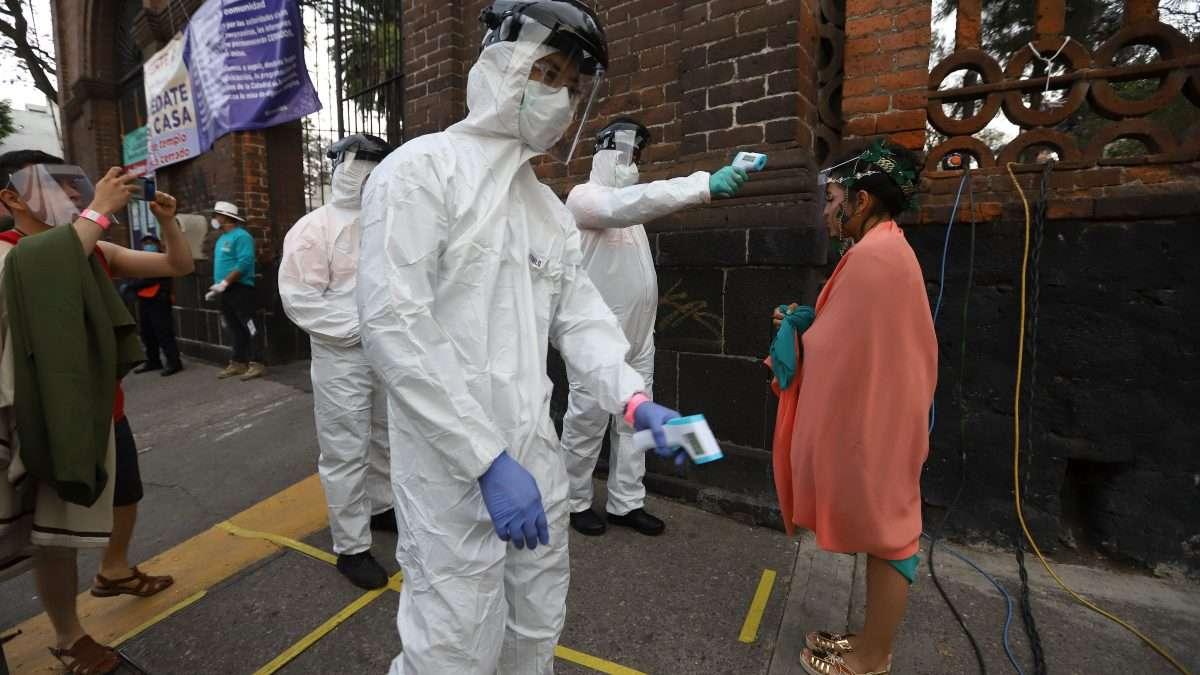 RITO SANITARIO. Personajes son sanitizados antes de entrar. Foto: Víctor Gahbler