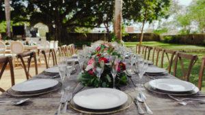 Mesa y sillas adornadas, con platos y cubierto, mantel y un arreglo de flores