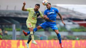 Dos jugadores de fútbol golpeando un balón