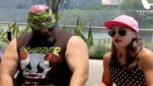 Luchador con máscara y chica con gafas de sol y gorra